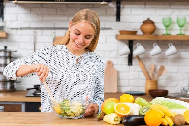 Tiro médio sorridente mulher fazendo uma salada