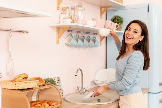 Tiro médio sorridente mulher lavando os pratos