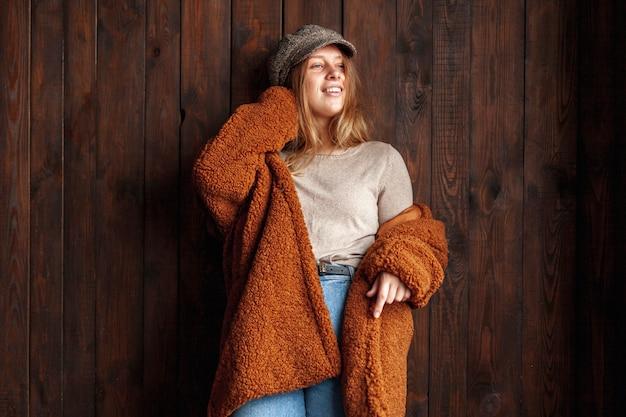 Tiro médio sorridente mulher posando com fundo de madeira