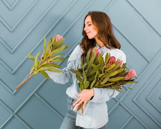 Tiro médio sorridente mulher segurando buquê de flores