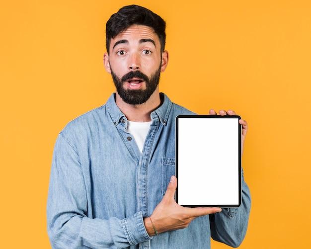 Tiro médio surpreendido cara segurando um tablet