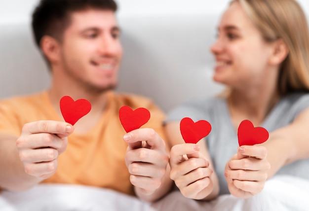Tiro médio turva casal segurando papel em forma de coração