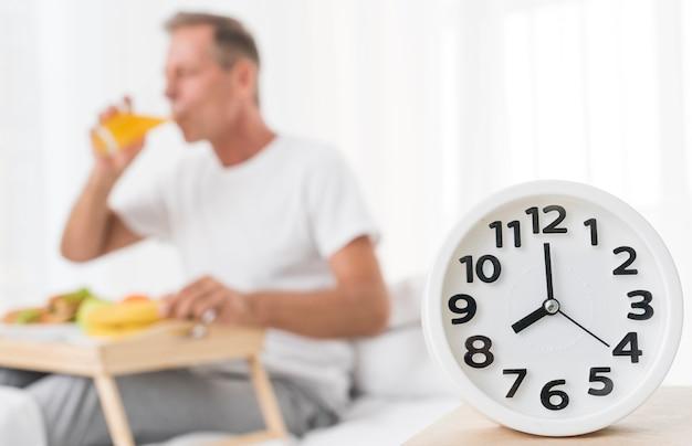 Tiro médio turva homem tomando café da manhã às 8 da manhã