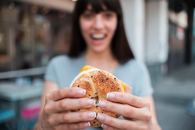 Tiro médio turva menina com hambúrguer