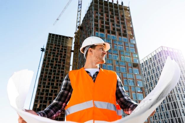 Tiro médio, vista baixa ângulo, de, engenheiro construção, segurando, planos