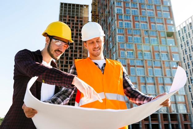 Tiro médio, vista baixa ângulo, de, engenheiro, e, arquiteta, supervisionando, construção