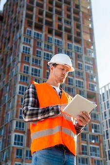 Tiro médio, vista baixa ângulo, engenheiro construção, olhar, tablete