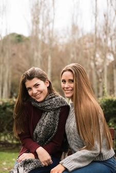 Tiro médio, vista lateral, de, dois, mulheres sorridentes, parque