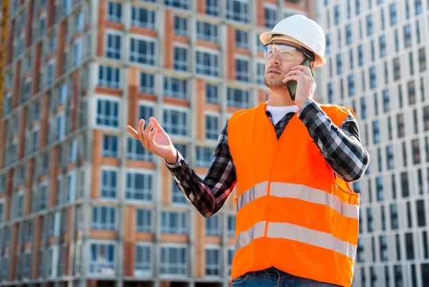 Tiro médio, vista lateral, de, engenheiro construção, conversa telefone