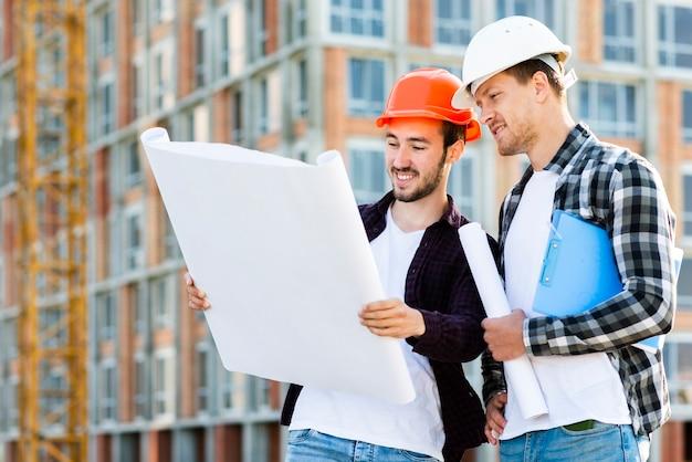 Tiro médio, vista lateral, de, engenheiro, e, arquiteta, supervisionando, construção
