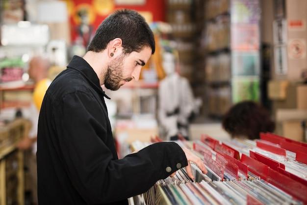 Tiro médio, vista lateral, de, homem jovem, olhando, vinils, em, loja