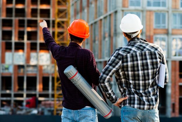 Tiro médio, vista traseira, de, engenheiro, e, arquiteta, supervisionando, construção