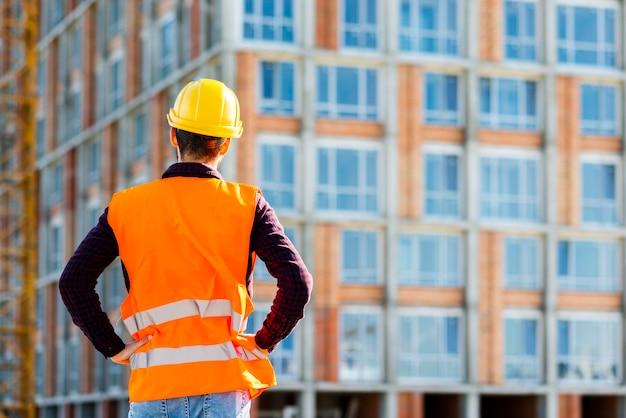 Tiro médio, vista traseira, de, engenheiro, supervisionando, construção