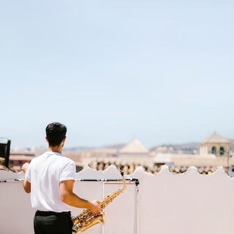 Tiro médio, vista traseira, homem, segurando, saxofone