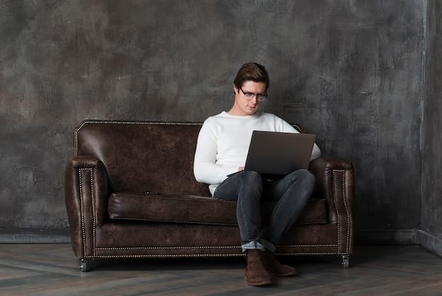 Tiro moderno homem trabalhando no laptop com espaço de cópia
