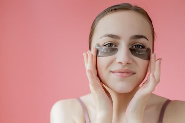 Tiro na cabeça, close-up, jovem sorridente com máscara de adesivos hidratantes sob os olhos