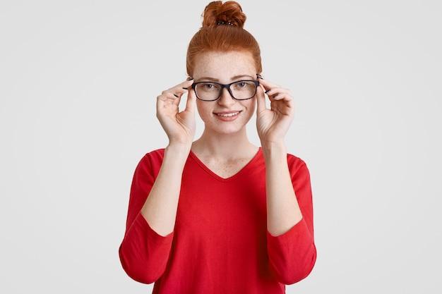 Tiro na cabeça da bela jovem sardenta europeia de óculos, tem um sorriso gentil, vestido de suéter vermelho