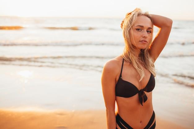 Tiro na cabeça da bela loira magro em um biquíni preto na praia oceano contra o sol. juventude, férias, viagens, moda.