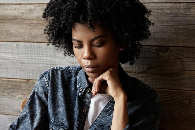 Tiro na cabeça da jovem mulher afro-americana atraente com cabelo afro, travesseiro, cabeça na mão, olhando para baixo, sentindo-se entediado ou sozinho enquanto passava o café da manhã sozinho no acolhedor café