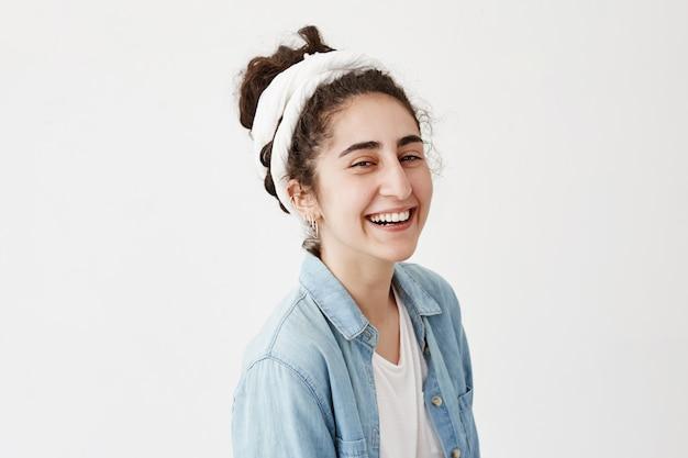 Tiro na cabeça da menina bonita com cabelos escuros e ondulados, usando bandana e camisa jeans elegante, sorrindo amplamente e demonstrando dentes brancos e uniformes, relaxando dentro de casa, posando contra parede branca