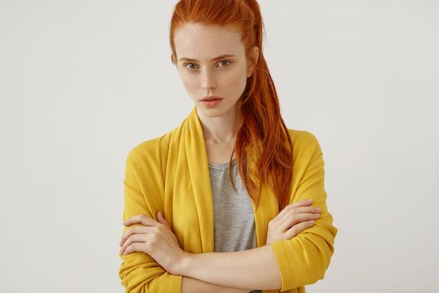 Tiro na cabeça da mulher ruiva jovem atraente com rabo de cavalo, olhando seriamente com seus olhos verdes, mantendo as mãos cruzadas, vestindo roupas amarelas isoladas. confiança