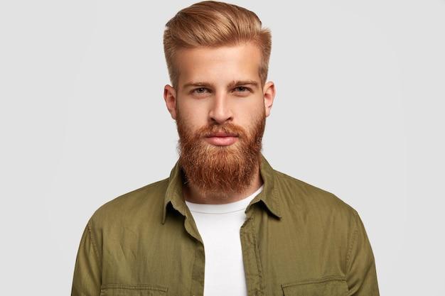Tiro na cabeça de atraente barbudo com penteado da moda, tem barba espessa e bigode raposa, olha sério, ouve com atenção as notícias do interlocutor, isolado sobre uma parede branca. conceito de estilo de vida
