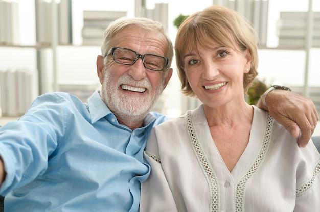 Tiro na cabeça de idosos caucasianos felizes com videochamada para a família ou amigos, relaxar em casa, sorrindo conceito dos avós aposentados sênior saudáveis, tiro na cabeça