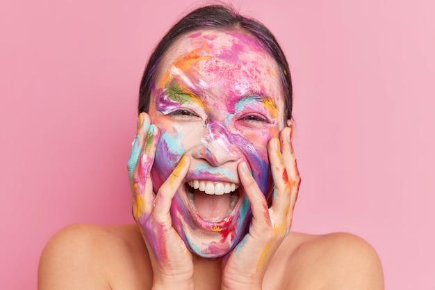 Tiro na cabeça de mulher étnica feliz e radiante mantém as mãos nas bochechas risos positivamente mantém a boca aberta com maquiagem criativa borrada no rosto com tintas de aquarela