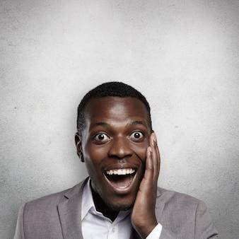 Tiro na cabeça de um atraente trabalhador de escritório afro-americano, segurando a mão em sua bochecha, gritando em choque, feliz e surpreso com a promoção inesperada no trabalho. conceito de negócios e carreira.