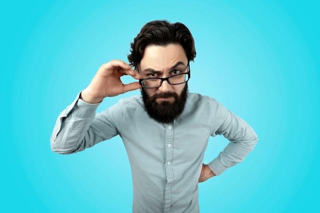 Tiro na cabeça de um homem agressivo estritamente irritado com barba, bigode, olha seriamente através dos óculos, franze a testa em insatisfação, expressa emoções negativas, sobre a parede azul