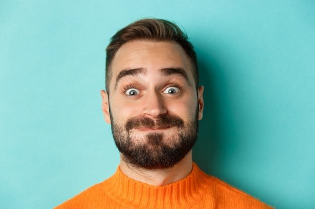 Tiro na cabeça de um homem barbudo engraçado mostrando rostos e fazendo beicinho, prendendo a respiração, de pé no suéter laranja contra fundo turquesa.