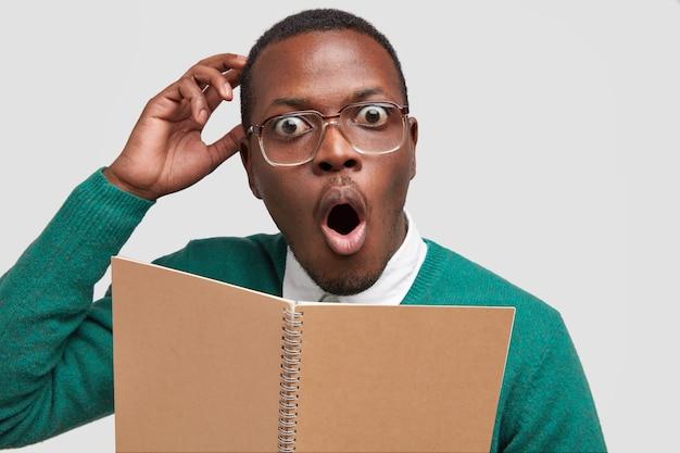 Tiro na cabeça de um homem de pele escura e emocional surpreso coça a cabeça, usa óculos ópticos, abre a boca amplamente, segura o bloco de notas, tem muitas tarefas para terminar
