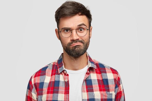 Tiro na cabeça de um jovem intrigado, indeciso e descontente com a barba por fazer, franze os lábios, tem expressão incerta, corte de cabelo na moda, usa camisa quadriculada, isolado sobre a parede branca. conceito de expressões faciais