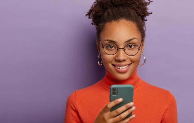 Tiro na cabeça de uma adorável mulher de pele escura e encaracolada usa telefone celular, sorri agradavelmente, usa óculos redondos, macacão laranja, isolado na parede roxa tecnologia, conceito de bate-papo