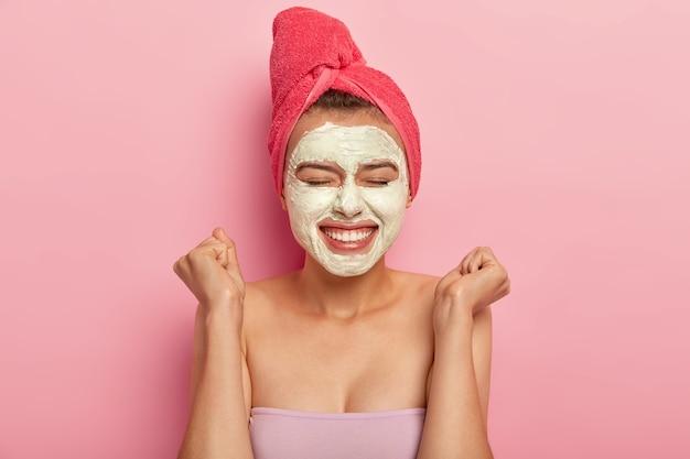 Tiro na cabeça de uma bela jovem levanta os punhos cerrados, aplica máscara hidratante no rosto, tem uma tez atraente e bem cuidada, usa produto de beleza natural para refrescar, embrulhado em toalha.