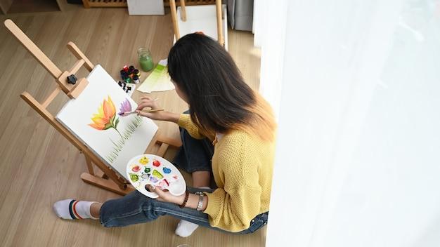 Tiro na cabeça de uma jovem artista feminina no suéter amarelo com a paleta na mão está pintando sobre tela no estúdio.
