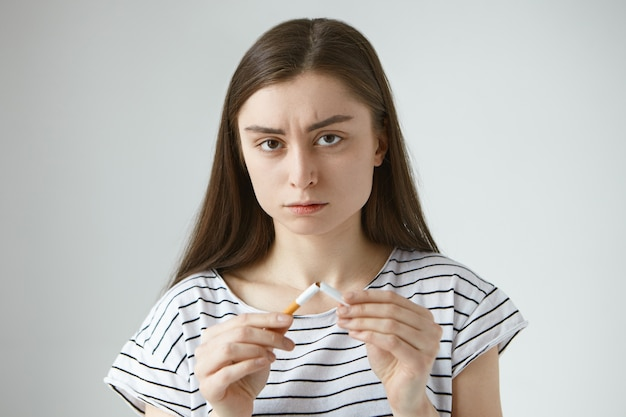 Tiro na cabeça de uma jovem europeia séria e séria com cabelos escuros em roupas casuais segurando duas metades de um cigarro quebrado nas mãos, parando de fumar e quebrando o hábito destrutivo ruim