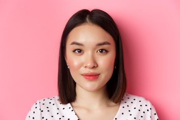 Tiro na cabeça de uma jovem mulher asiática feminina com penteado curto, olhando para a câmera, em pé rosa.