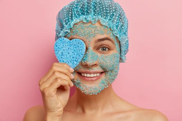 Tiro na cabeça de uma mulher bonita e satisfeita aplica esfoliante com sal marinho, segura uma esponja cosmética em forma de coração, faz tratamentos de beleza, pele nua