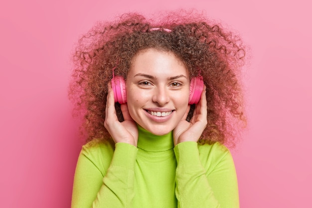 Tiro na cabeça de uma mulher européia bonita com cabelo crespo cacheado usa fones de ouvido estéreo e escuta faixa de áudio com clima otimista vestido com gola olímpica casual isolada sobre a parede rosa.