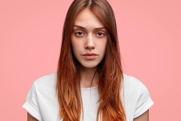 Tiro na cabeça de uma mulher sardenta séria pensativa olha diretamente para a câmera, tem cabelo comprido, usa camiseta branca casual, posa contra o fundo rosa do estúdio.