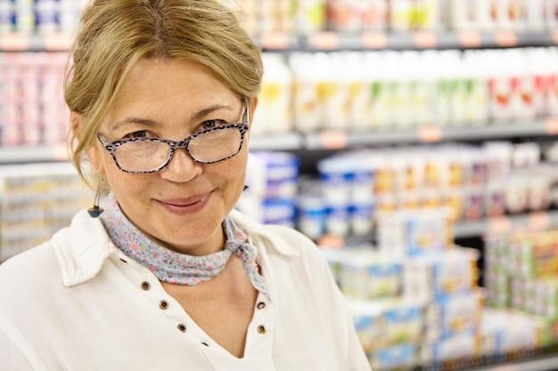 Tiro na cabeça do cliente feminino caucasiano maduro, andando pelo hipermercado, procurando produtos frescos e saborosos para preparar um jantar em casa perfeito e delicioso para toda a família