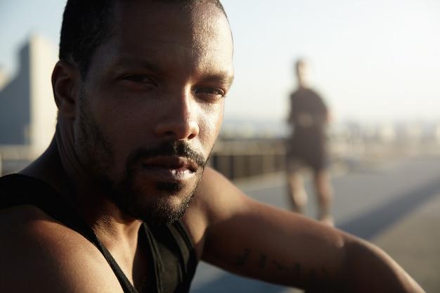 Tiro na cabeça do corredor de homem afro-americano descansando após treino intensivo ao ar livre e treino