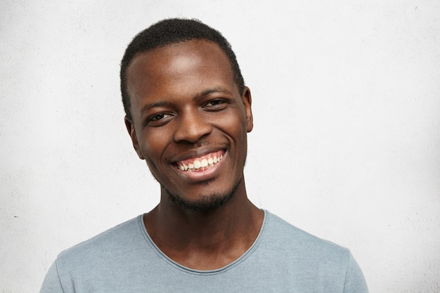 Tiro na cabeça do homem afro-americano jovem bonito olhando com amplo sorriso amigável, aproveitando o bom dia e tempo de lazer dentro de casa. homem negro, sentindo-se feliz e despreocupado enquanto relaxa em casa