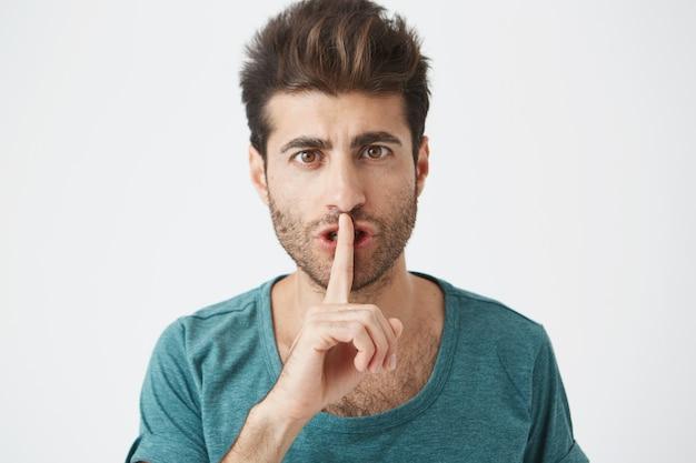 Tiro na cabeça do homem caucasiano elegante elegante casual camiseta azul, segurando o dedo indicador nos lábios, pedindo para manter o silêncio na biblioteca.