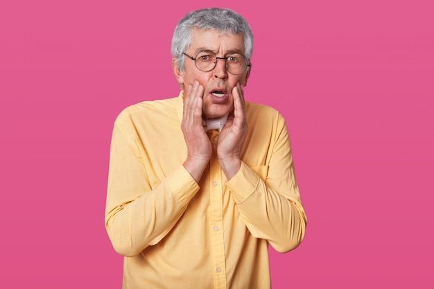 Tiro na cabeça do homem magro aterrorizado estupefato veste camisa amarela, mantém as mãos nas bochechas. homem idoso surpreso com óculos contra parede rosa