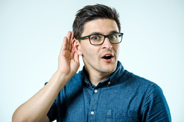 Tiro na cabeça do homem tentando ouvir fofocas ou notícias. isolado em fundo cinza