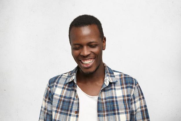 Tiro na cabeça do jovem afro-americano tímido e atraente em roupas da moda, fechando os olhos e sorrindo amplamente, mostrando os dentes retos e brancos