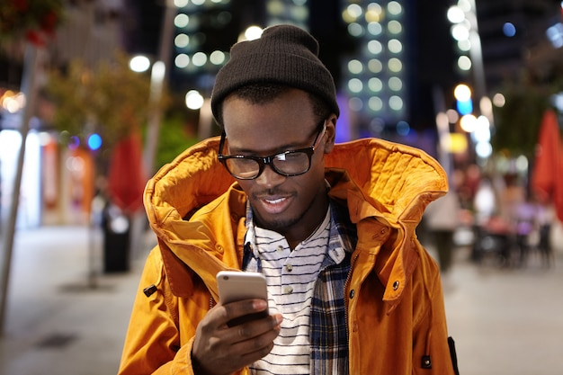 Tiro na cabeça do jovem estudante afro-americano bonito andando pela cidade à noite, segurando o telefone móvel, usando wifi urbano, navegando em fotos nas mídias sociais. comunicação e tecnologia moderna