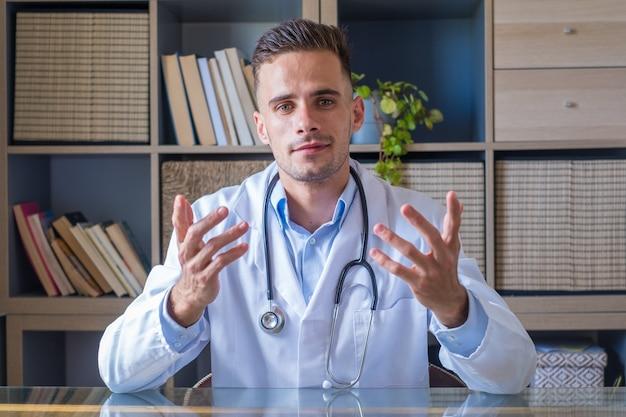 Tiro na cabeça do jovem médico usando óculos e uniforme branco com estetoscópio falando, consultando o paciente online, olhando para a câmera, fazendo videochamada, sentado à mesa no escritório
